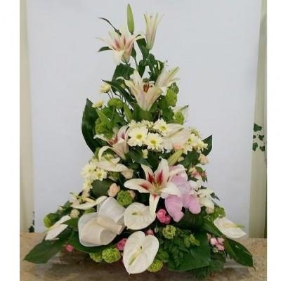 Centro de flor variada con lilium, antutium, margaritas, con alguna rosa y verdes variados. (sujeto a modificaciones, según temporada y stock)